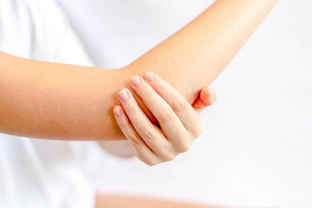 Billede illustrerer kvinde der modtager behandling af golfalbue eller tennisalbue